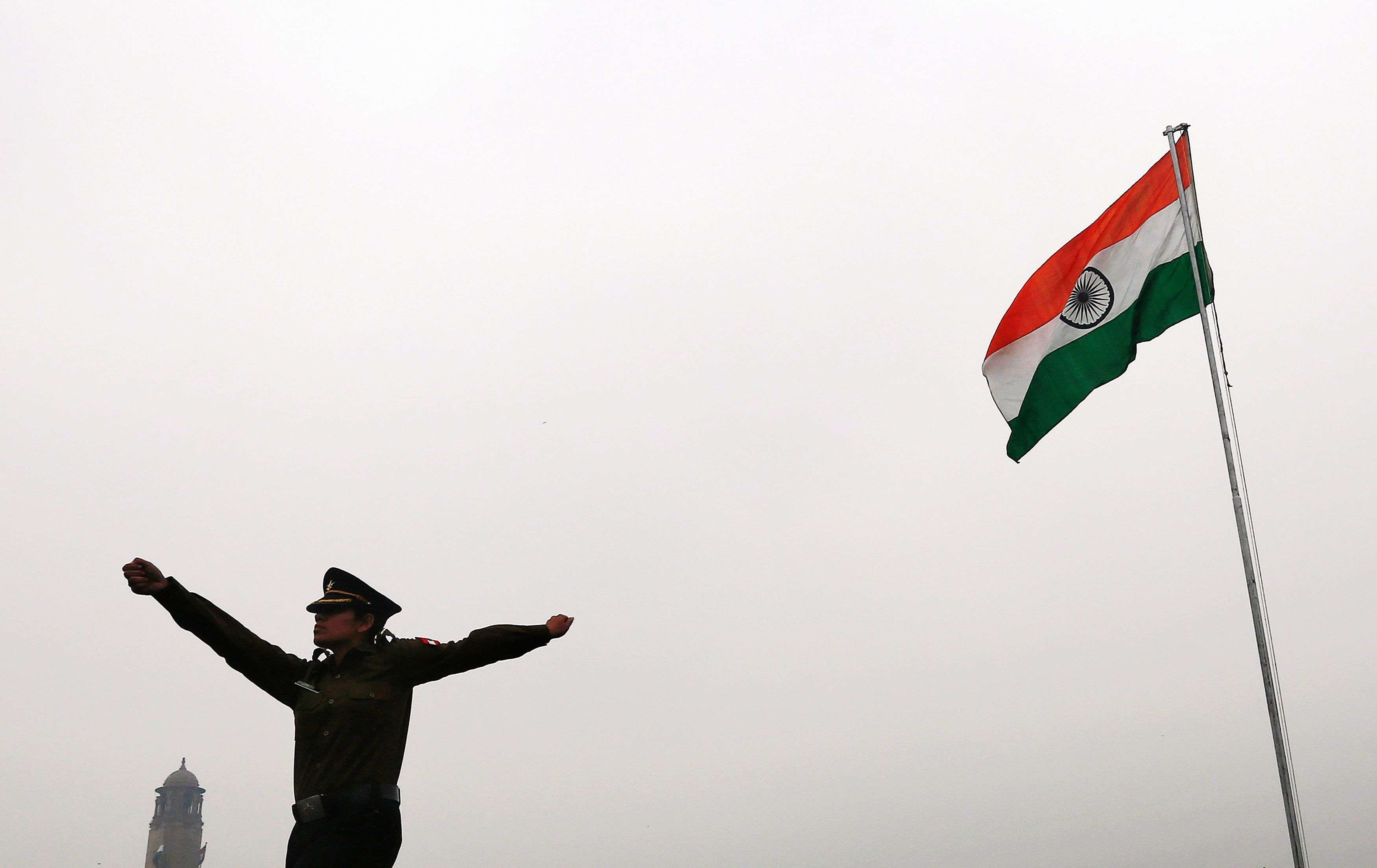 A soldier marches as India's national flag flutters during a rehearsal for the 'Beating the Retreat' ceremony in New Delhi. (REUTERS/Adnan Abidi)