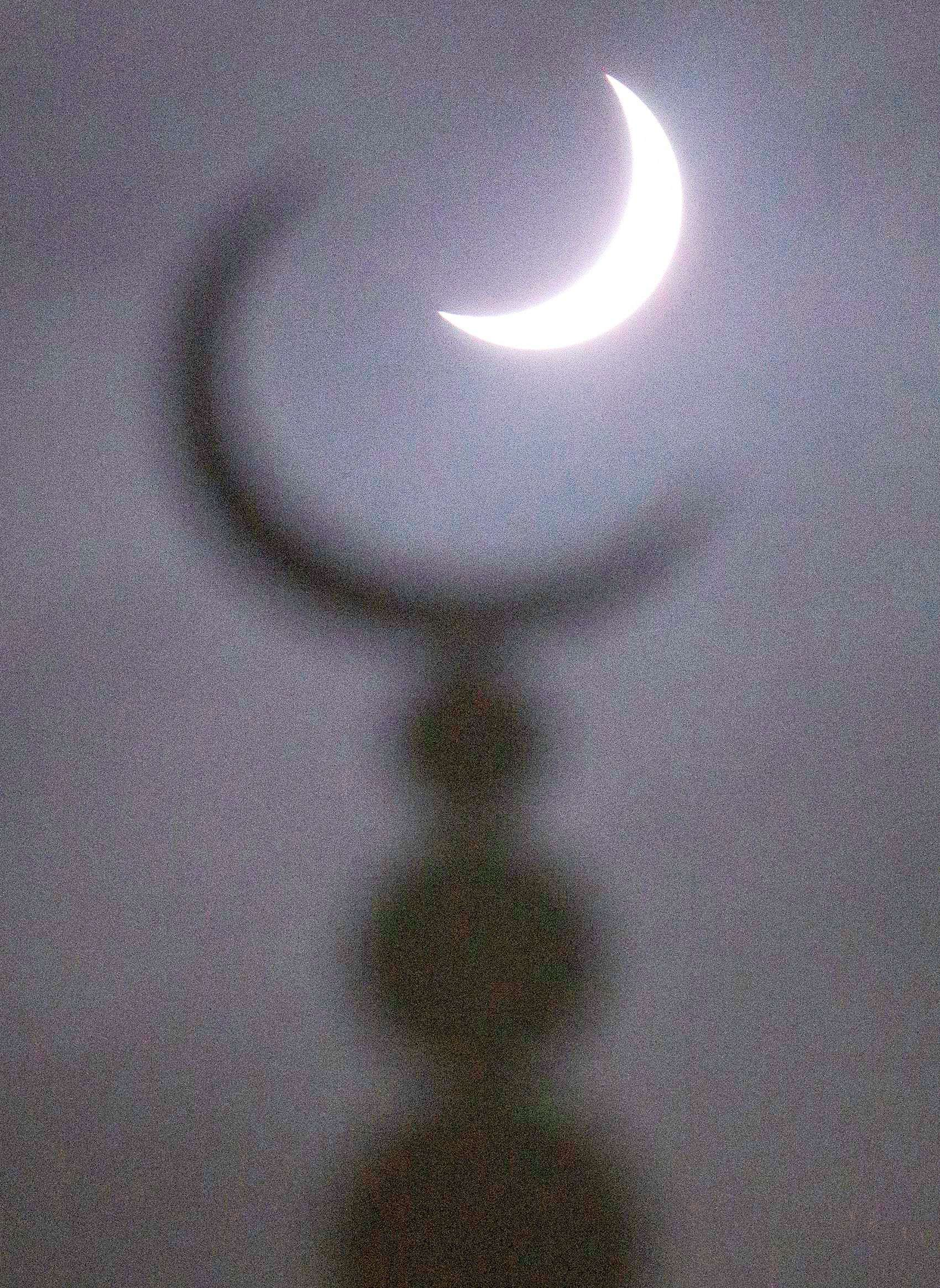 A partial solar eclipse in seen above a mosque in Oxford, central England. (REUTERS/Eddie Keogh)