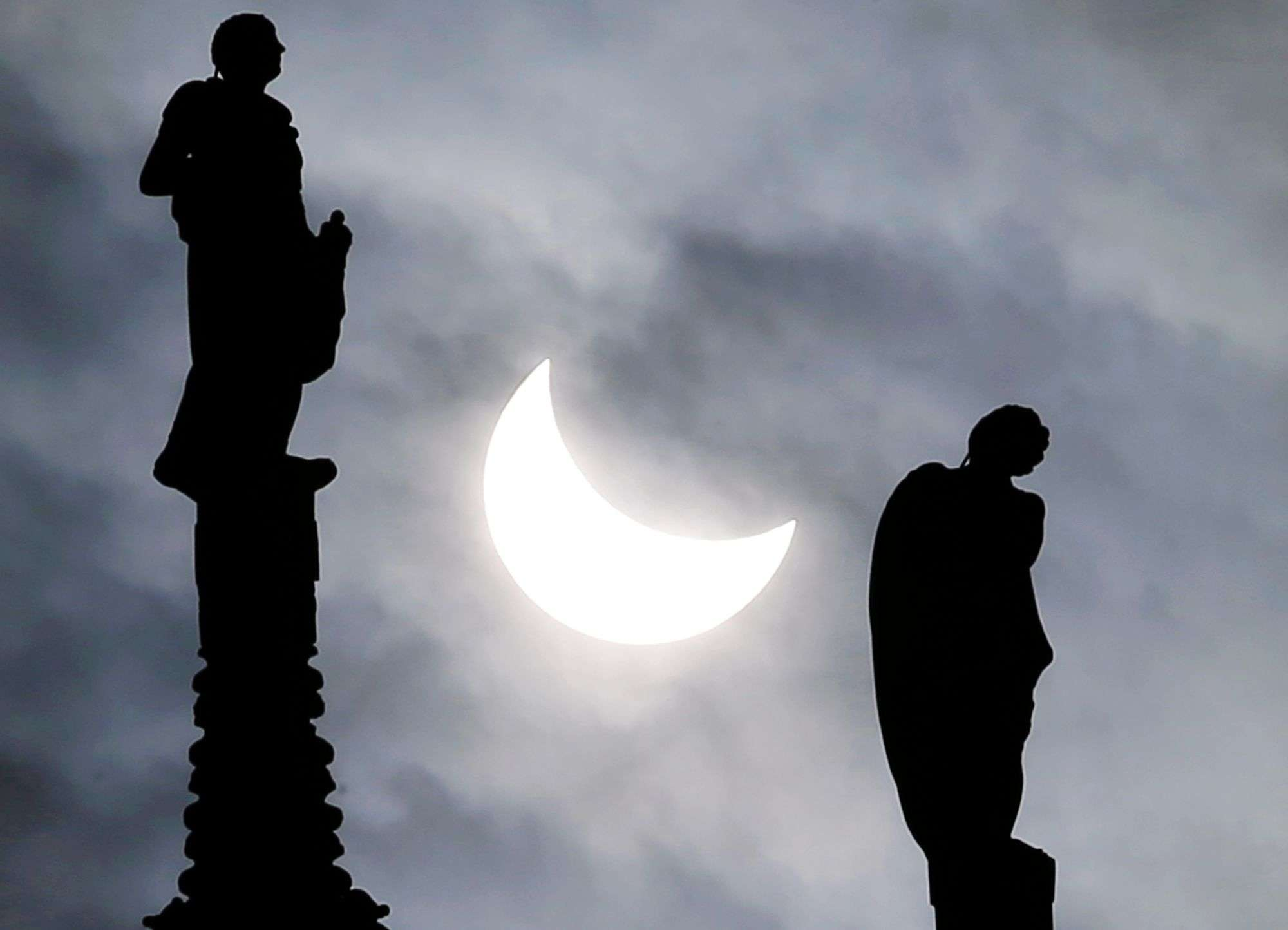 The sun is seen during an eclipse between two statues of the Duomo gothic cathedral in Milan, Italy. (AP Photo/Antonio Calanni)