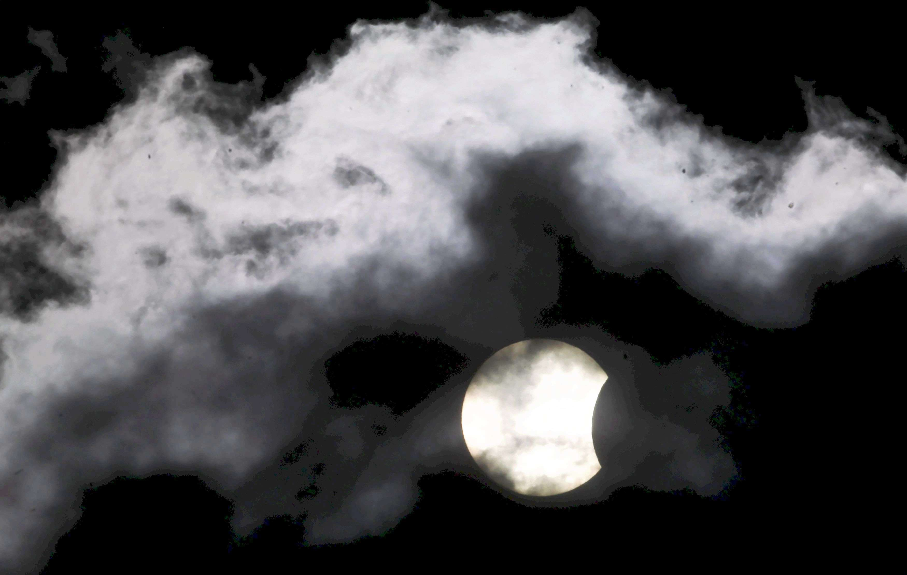 A partial solar eclipse is seen through clouds in Sarajevo. (REUTERS/Dado Ruvic)