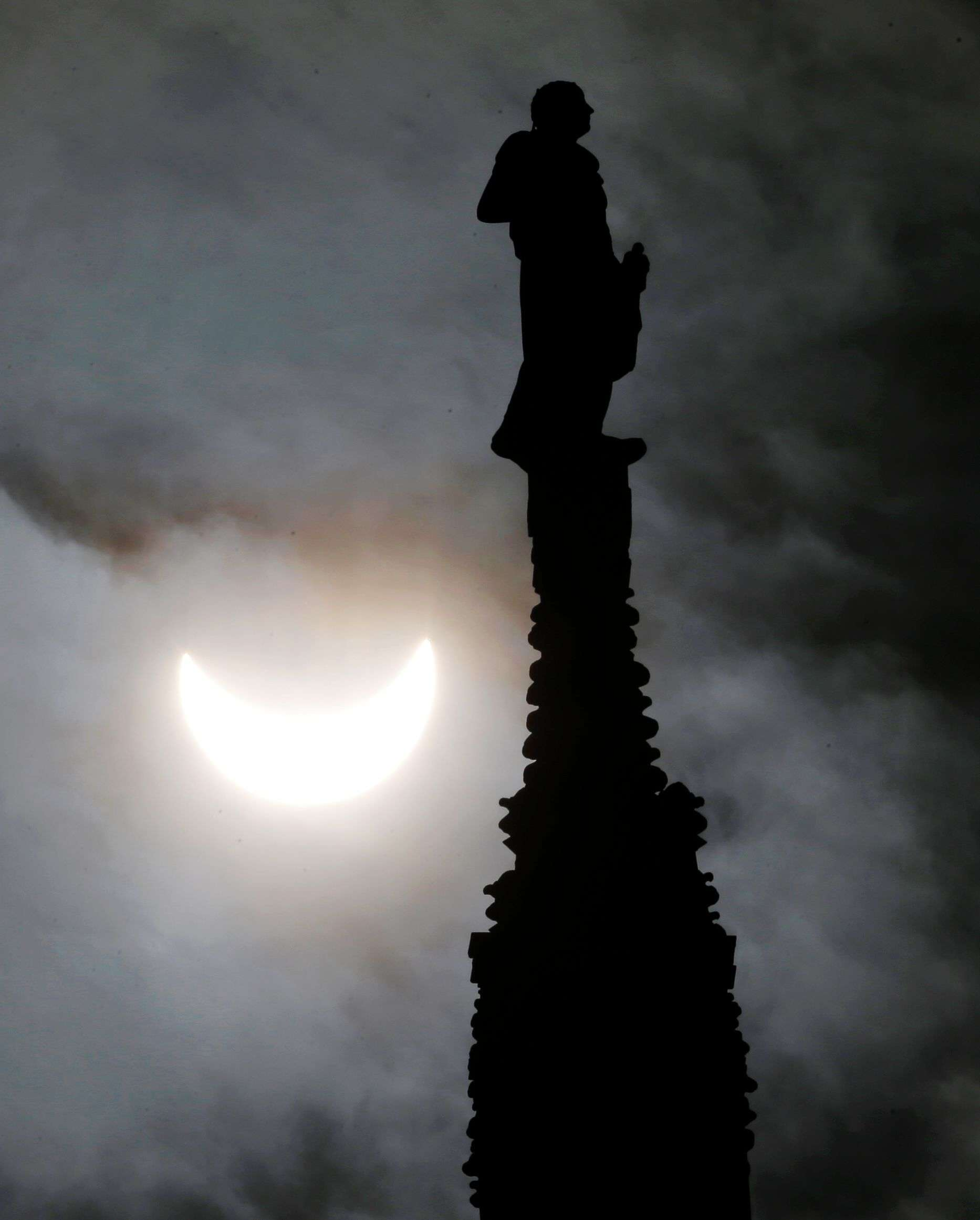 The moon starts to block the sun during a solar eclipse next to a statue of the Duomo gothic cathedral in Milan, Italy. (AP Photo/Antonio Calanni)