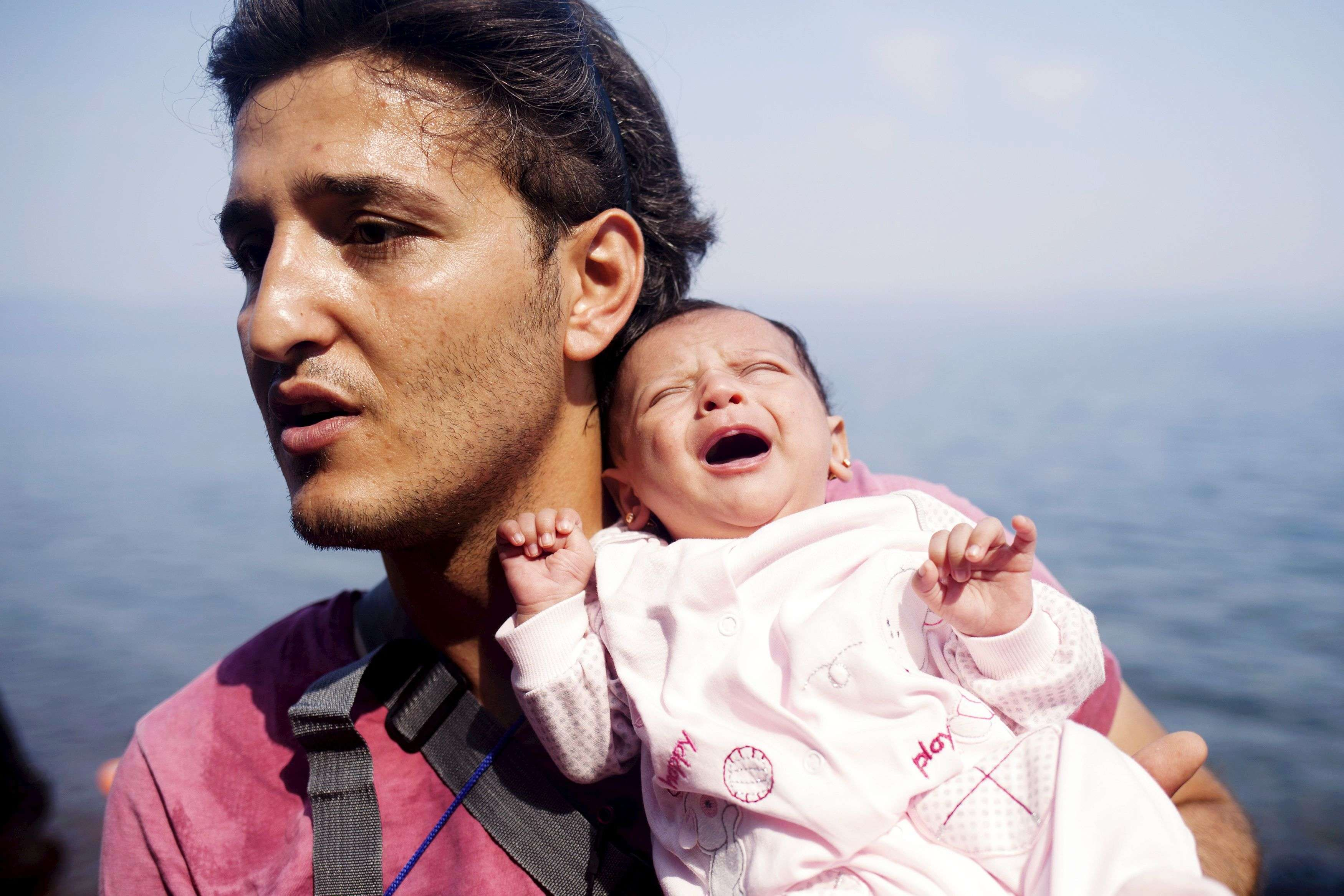 A Syrian refugee from Aleppo holds his one month old daughter moments after arriving on a dinghy on the Greek island of Lesbos. (REUTERS/Dimitris Michalakis)