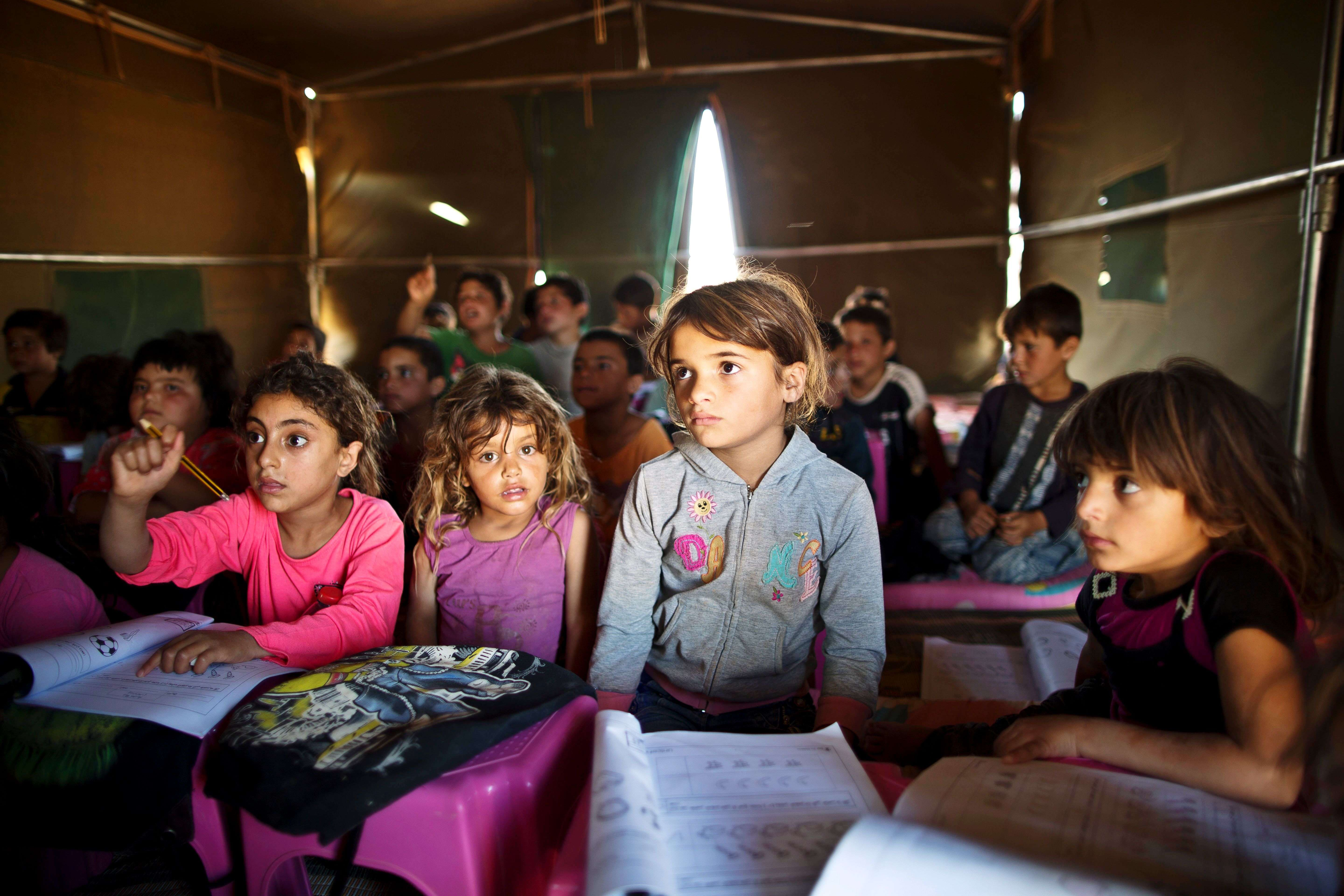 Syrian refugee children attend a class at a makeshift school set up in a tent at an informal tented settlement near the Syrian border on the outskirts of Mafraq, Jordan. (AP Photo/Muhammed Muheisen, File)