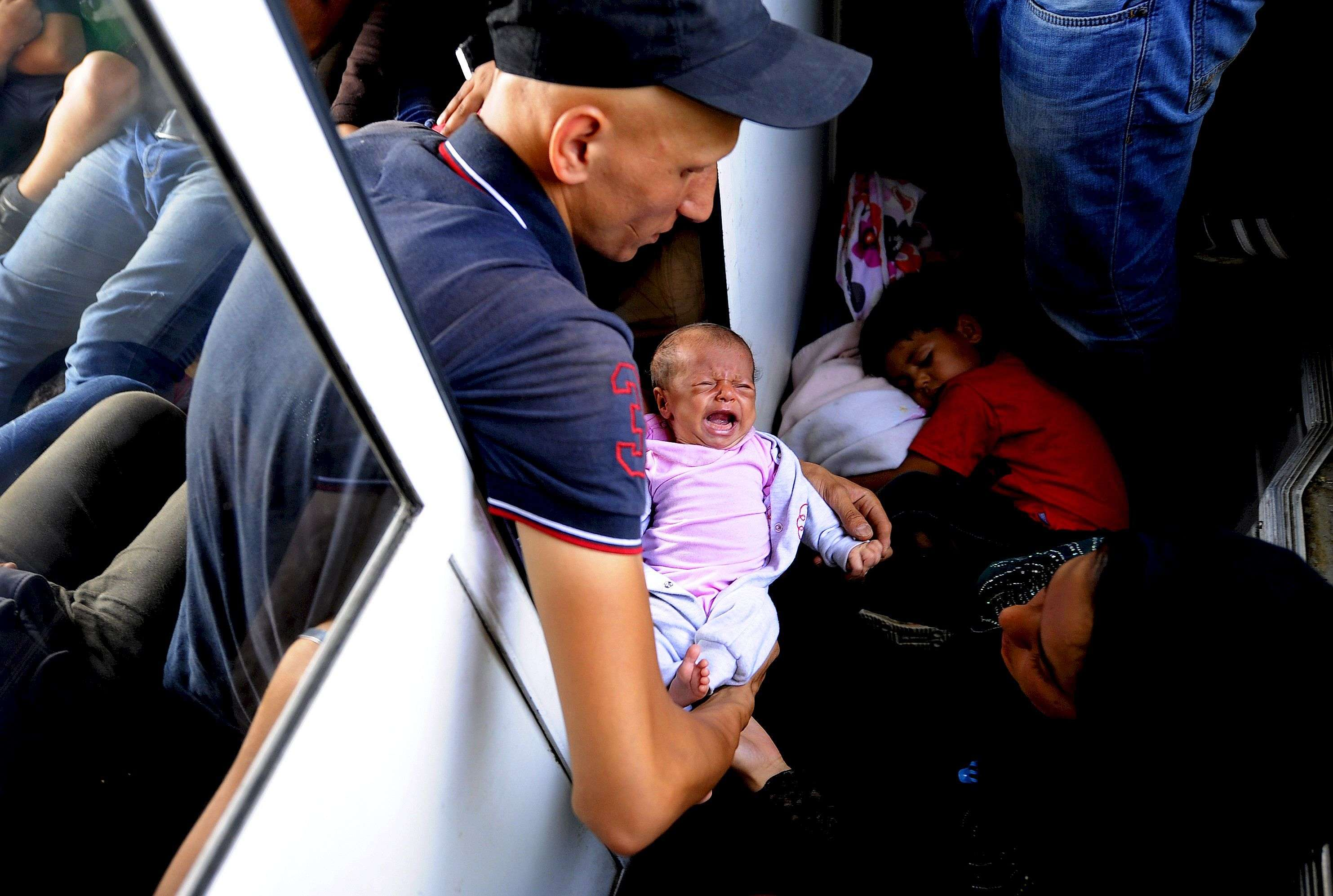 "A migrant from Aleppo, Syria holds his 30-day-old baby on an overcrowded train as they travel through Macedonia August 2, 2015. Tens of thousands of migrants, mainly from the Middle East and Africa, use the Balkans route to get into the European Union, passing from Greece to Macedonia and Serbia and then to western Europe. After walking across the border into Macedonia to the small local station of Gevgelia, migrants pile onto an overcrowded four-carriage train in sweltering heat, young infants among them, to travel about 200 km north. Their aim: to enter Serbia on foot, another step in their uncertain search for a better life.  REUTERS/Ognen Teofilovski TPX IMAGES OF THE DAYPICTURE 24 OF 33 FOR WIDER IMAGE STORY ""MIGRANTS: A TRAIN TOWARDS A NEW LIFE""SEARCH ""TEOFILOVSKI TRAIN"" FOR ALL PICTURES"
