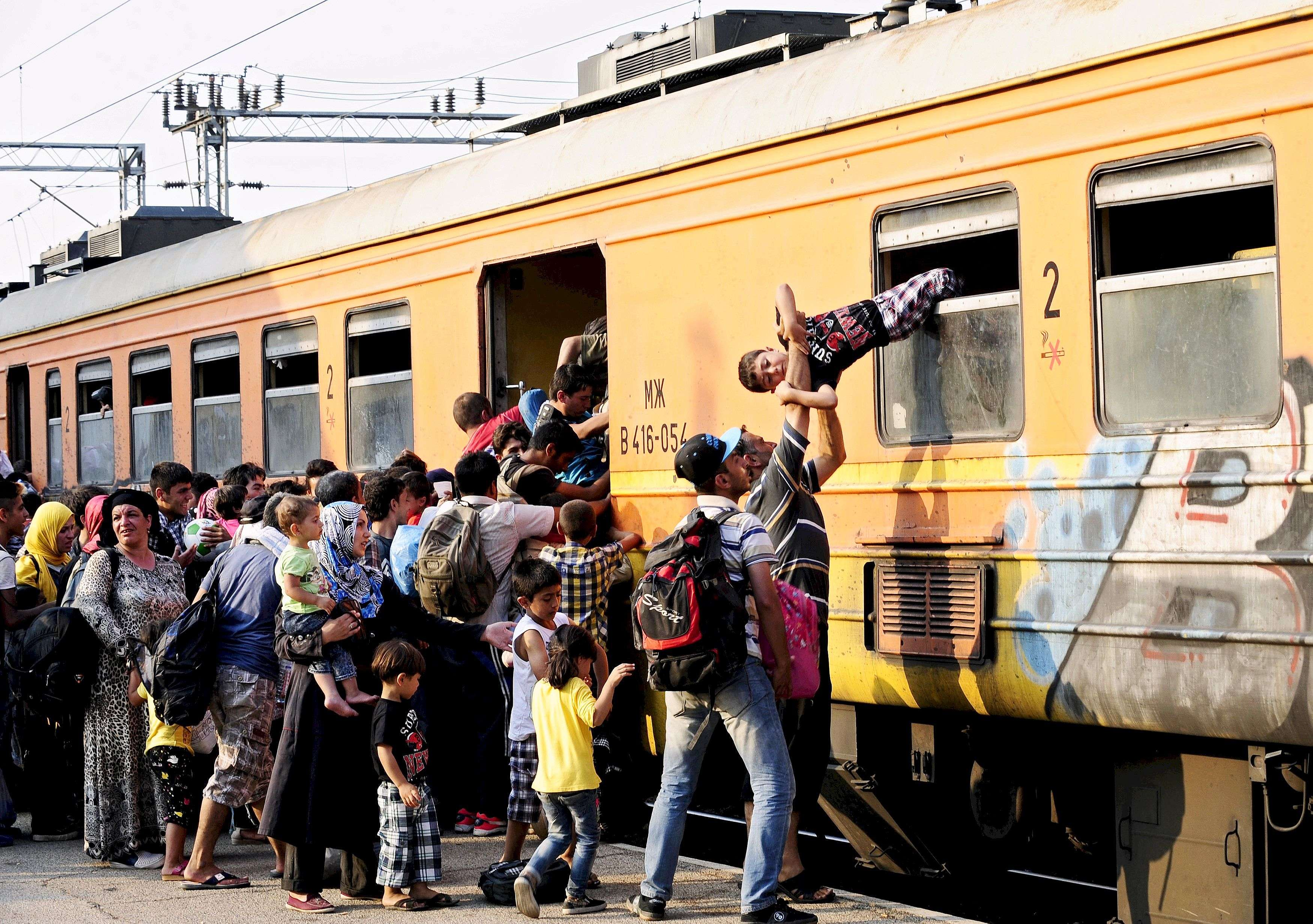 "Migrants clamber onto a train at Gevgelija train station in Macedonia, close to the border with Greece July 30, 2015. Tens of thousands of migrants, mainly from the Middle East and Africa, use the Balkans route to get into the European Union, passing from Greece to Macedonia and Serbia and then to western Europe. After walking across the border into Macedonia to the small local station of Gevgelia, migrants pile onto an overcrowded four-carriage train in sweltering heat, young infants among them, to travel about 200 km north. Their aim: to enter Serbia on foot, another step in their uncertain search for a better life.  REUTERS/Ognen Teofilovski TPX IMAGES OF THE DAYPICTURE 16 OF 33 FOR WIDER IMAGE STORY ""MIGRANTS: A TRAIN TOWARDS A NEW LIFE""SEARCH ""TEOFILOVSKI TRAIN"" FOR ALL PICTURES"