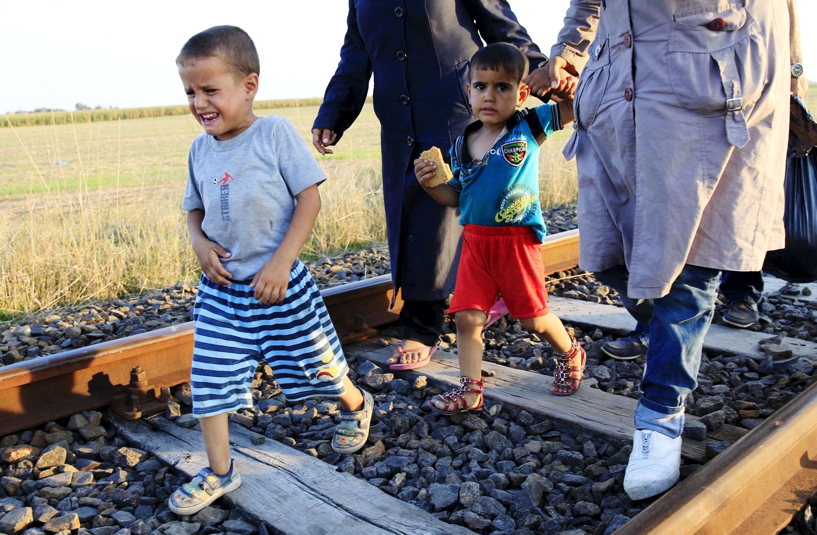 A migrant boy cries as he walks on a railway track after he crossed the Hungarian-Serbian border near Roszke. (REUTERS/Bernadett Szabo)