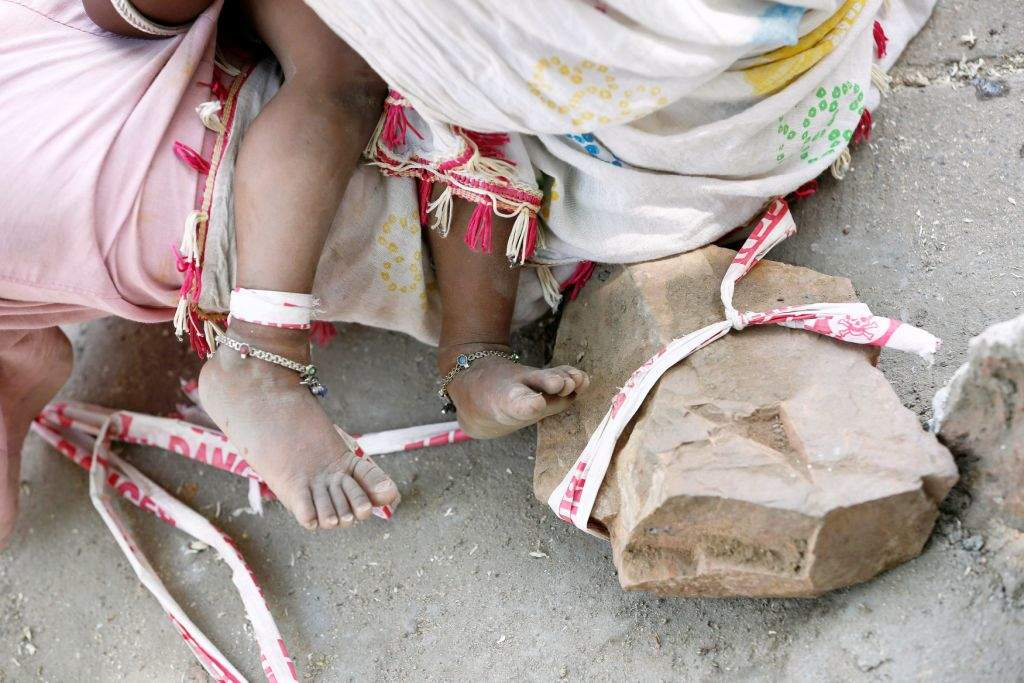 "Sarta Kalara feeds her 15-month-old Shivani as one end of a barrier tape is tied to Shivani's foot and the other end to a stone to prevent Shivani from running away, when she works at a construction site nearby, in Ahmedabad, India, April 19, 2016. Kalara says she has no option but to tether her daughter Shivani to a stone despite her crying, while she and her husband work for 250 rupees ($3.8) each a shift digging holes for electricity cables in the city of Ahmedabad. There are about 40 million construction workers in India, at least one in five of them women, and the majority poor migrants who shift from site to site, building infrastructure for India's booming cities. Across the country it is not uncommon to see young children rolling in the sand and mud as their parents carry bricks or dig for new roads or luxury houses. REUTERS/Amit Dave       SEARCH ""TIED TODDLER"" FOR THIS STORY. SEARCH ""THE WIDER IMAGE"" FOR ALL STORIES"