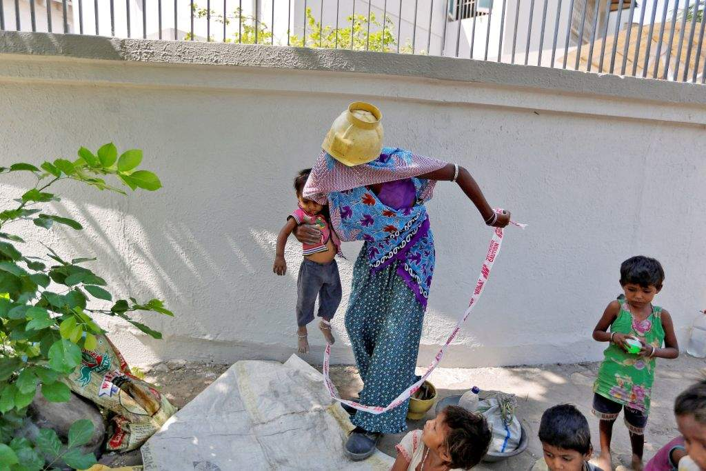 "Sarta Kalara, a construction worker, holds her 15-month-old Shivani as a barrier tape is tied to Shivani's ankle to prevent her from running away when Kalara works nearby in Ahmedabad, India, April 20, 2016. Kalara says she has no option but to tether her daughter Shivani to a stone despite her crying, while she and her husband work for 250 rupees ($3.8) each a shift digging holes for electricity cables in the city of Ahmedabad. There are about 40 million construction workers in India, at least one in five of them women, and the majority poor migrants who shift from site to site, building infrastructure for India's booming cities. Across the country it is not uncommon to see young children rolling in the sand and mud as their parents carry bricks or dig for new roads or luxury houses. REUTERS/Amit Dave       SEARCH ""TIED TODDLER"" FOR THIS STORY. SEARCH ""THE WIDER IMAGE"" FOR ALL STORIES"