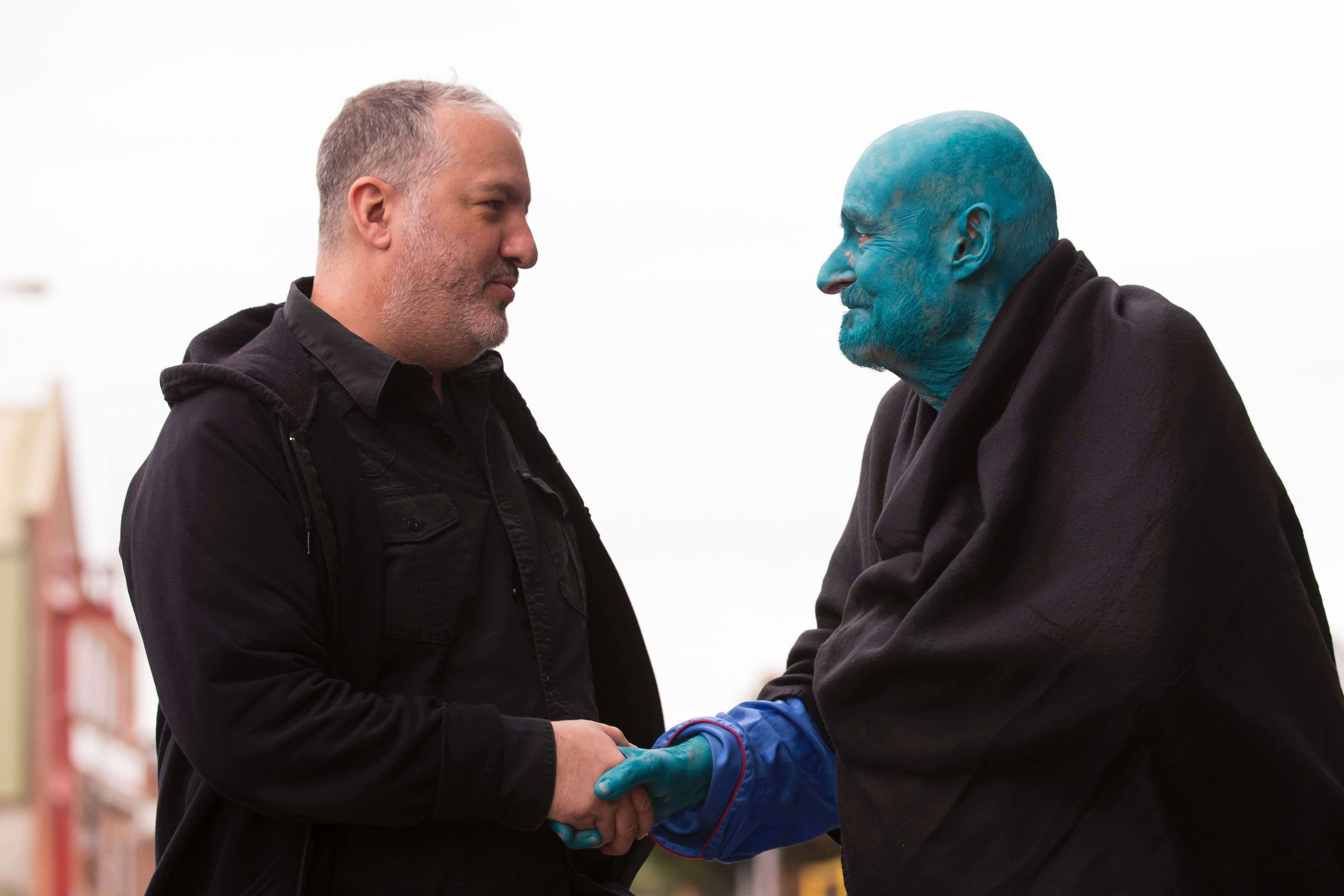 """US artist Spencer Tunick (L), shakes hands with 80 year old Belgian, Arizona-based art collector Stephane Janssen who has participated in 20 of Turnick's installations after around 3000 naked volunteers, painted in blue to reflect the colours found in Marine paintings in Hull's Ferens Art Gallery, participate in US artist, Spencer Tunick's """"Sea of Hull"""" installation on the Scale Lane swing bridge in Kingston upon Hull on July 9, 2016. Over a period of 20 years, the New York based artist has created over 90 art installations in some of the most culturally significant places and landmarks around the world including the Sydney Opera House, Place des Arts in Montreal, Mexico City, Ernest Happel Stadium in Vienna and Munich in Germany. / AFP PHOTO / JON SUPER / RESTRICTED TO EDITORIAL USE - MANDATORY MENTION OF THE ARTIST UPON PUBLICATION - TO ILLUSTRATE THE EVENT AS SPECIFIED IN THE CAPTION - NO CLOSE UP SHOTS TO BE REPRODUCED OF INDIVIDUALS INVOLVED IN THE INSTALLATION"""