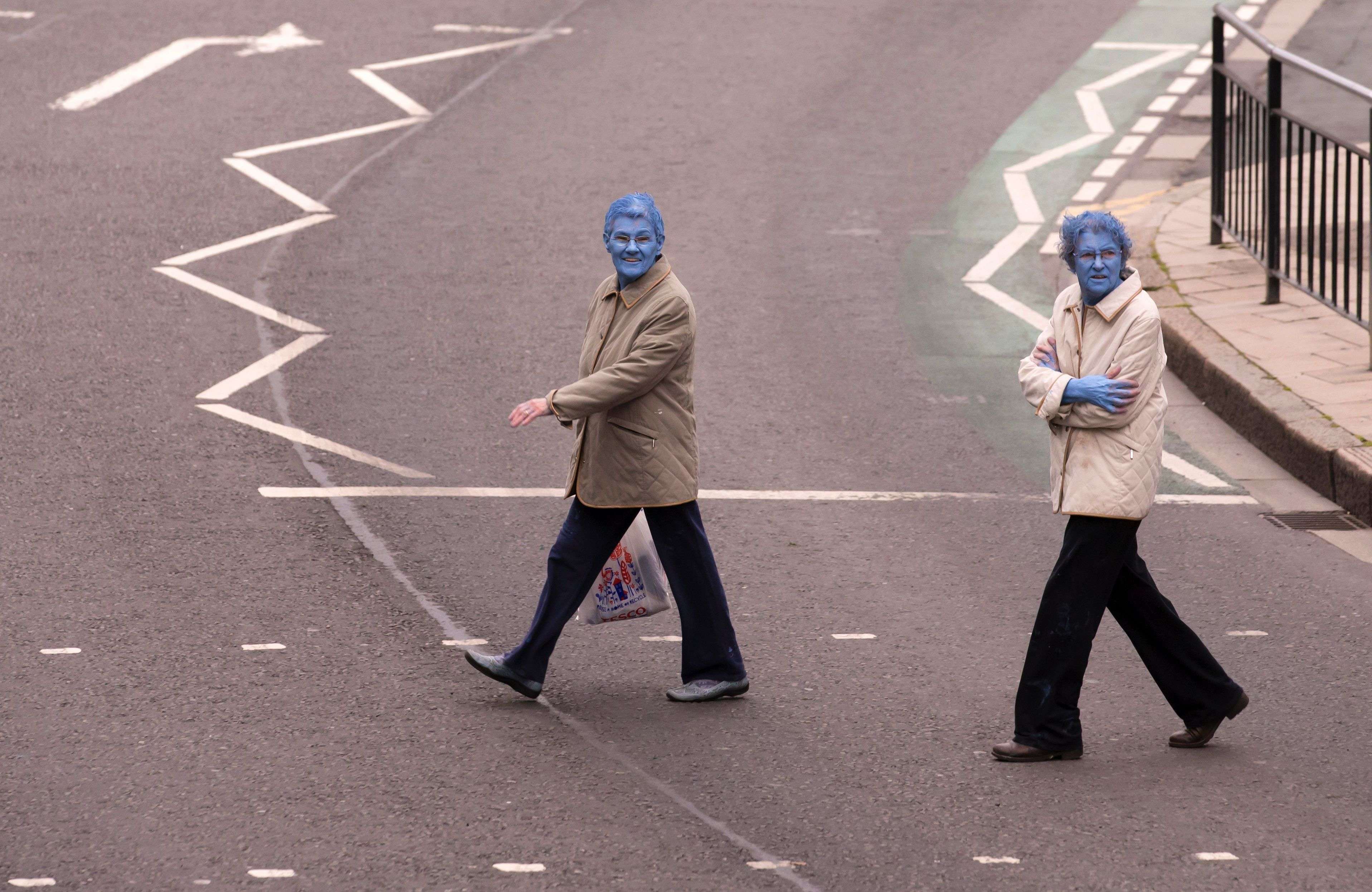 """After taking part in Spencer Tunick's """"Sea of Hull"""" installation, two women cross the road in Kingston upon Hull on July 9, 2016. Over a period of 20 years, the New York based artist has created over 90 art installations in some of the most culturally significant places and landmarks around the world including the Sydney Opera House, Place des Arts in Montreal, Mexico City, Ernest Happel Stadium in Vienna and Munich in Germany. / AFP PHOTO / JON SUPER / RESTRICTED TO EDITORIAL USE - MANDATORY MENTION OF THE ARTIST UPON PUBLICATION - TO ILLUSTRATE THE EVENT AS SPECIFIED IN THE CAPTION - NO CLOSE UP SHOTS TO BE REPRODUCED OF INDIVIDUALS INVOLVED IN THE INSTALLATION"""