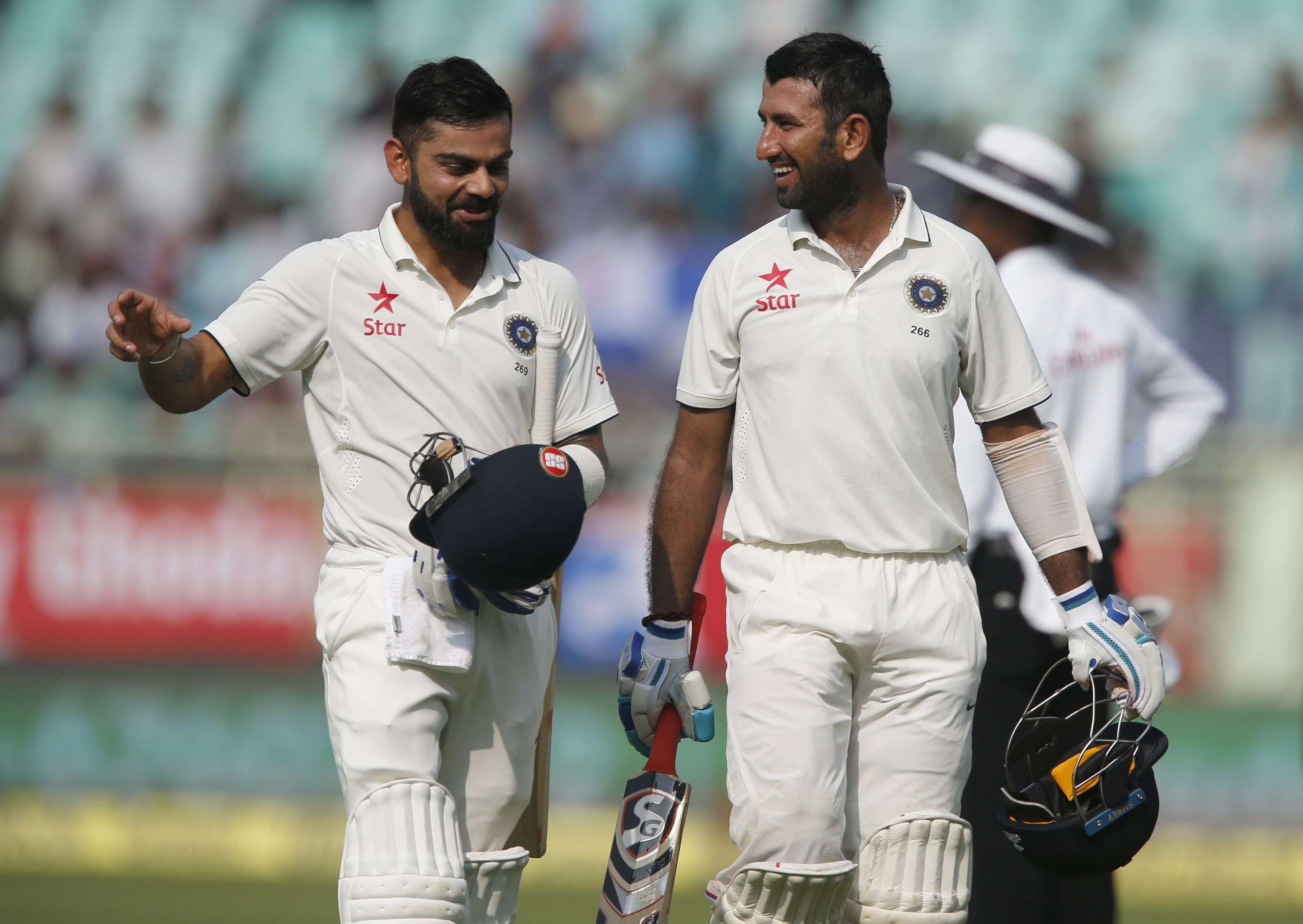 India's captain Virat Kohli, left, and Cheteshwar Pujara laugh as they leave the ground after a dog ran into the field during their first day of second cricket test match against England in Visakhapatnam, India, Thursday, Nov. 17, 2016. (AP Photo/Aijaz Rahi)