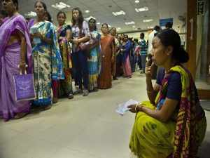 A woman takes rest after feeling unwell while waiting at a currency exchange counter at a bank in Gauhati, India, Friday, Nov. 11, 2016. People queued up outside banks for the second day to exchange currency notes after Indian Prime Minister Narendra Modi, delivering one of India's biggest-ever economic upsets, declared that the bulk of Indian currency notes no longer held any value and asked anyone holding those bills to take them to banks to deposit or exchange them. (AP Photo/ Anupam Nath)