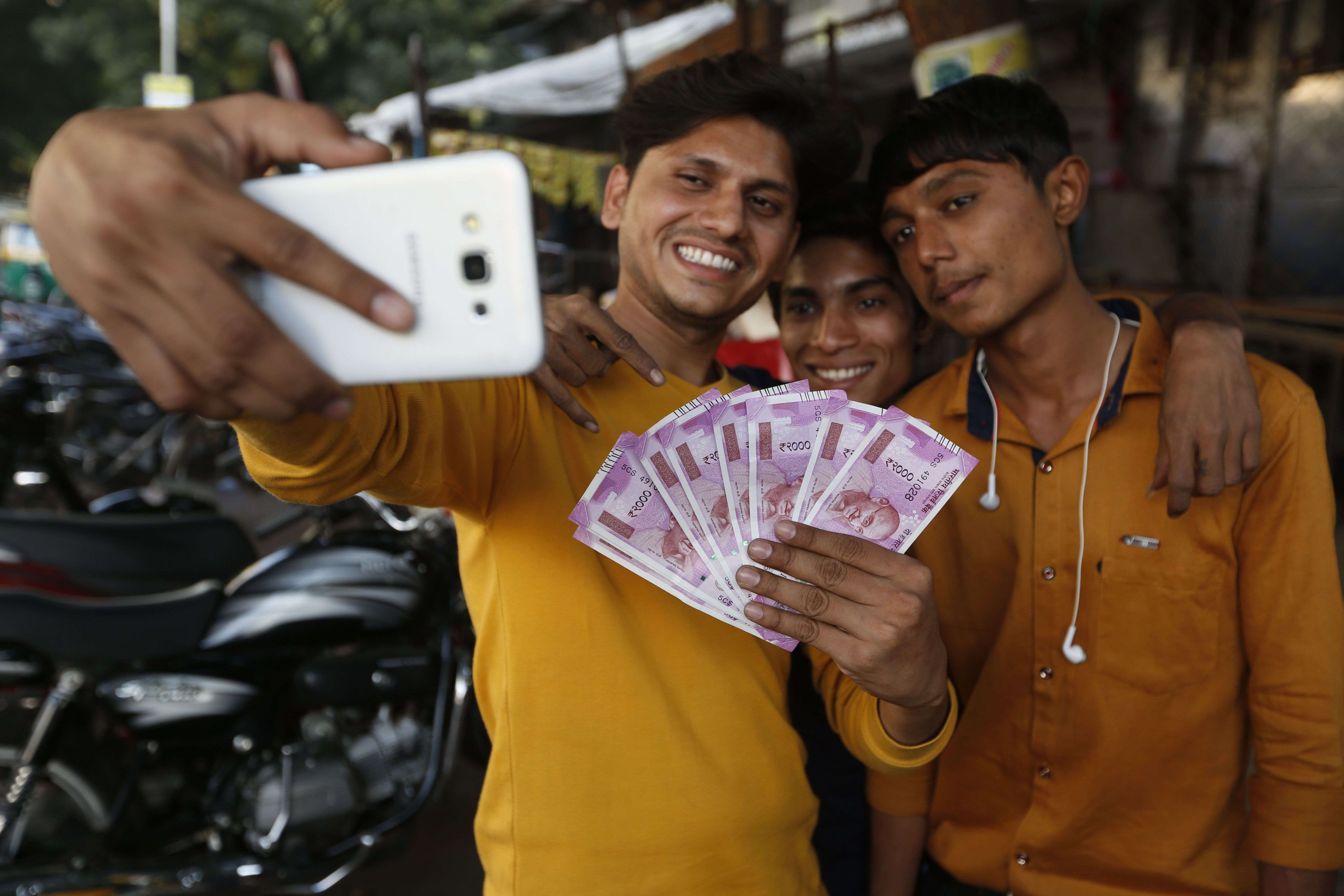 Indians takes selfie with new currency notes of 2000 Indian rupee in Ahmadabad, India, Friday, Nov. 11, 2016. Delivering one of India's biggest-ever economic upsets, Prime Minister Narendra Modi this week declared the bulk of Indian currency notes no longer held any value and told anyone holding those bills to take them to banks to deposit or exchange them. (AP Photo/Ajit Solanki)