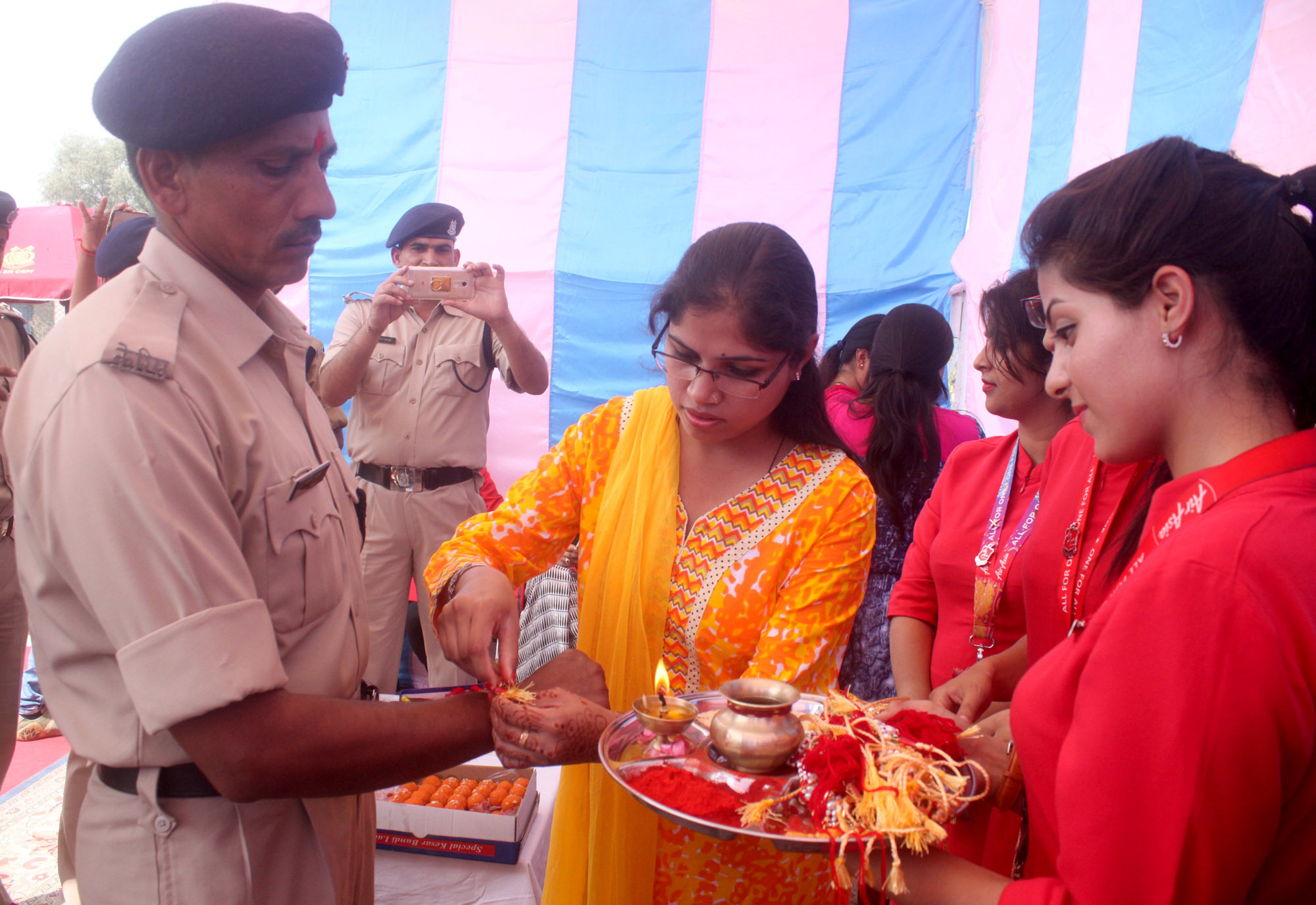 For the jawans posted in Kashmir Valley, away from their homes, girls tie rakhi on the wrists of CRPF personnel at Srinagar Airport.