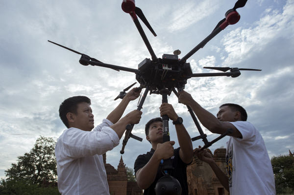 Nyi Lin Seck (L) and his team handle a drone carrying a 360 degrees 4K video camera before releasing it in flight to document the crumbling 700-year-old walls of the ancient city of Bagan. AFP