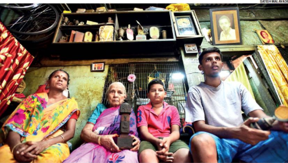 From left: Ashok Khale's wife Jayshree, his mother Kamala, and his two sons Harsh and Prathamesh, sit below the shelves filled with Khale's cycling trophies. Khale refused to let anyone polish or clean his trophies and medals