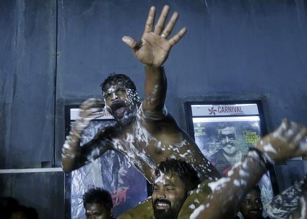 Fans continue celebrations outside a theatre in Mumbai. Photo: AP