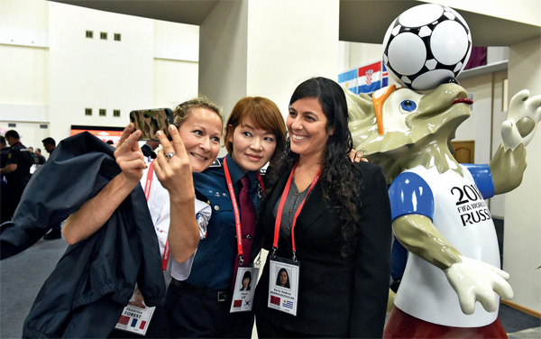 Police officers — Ekaterina Forest (France), Jihyun Lee (South Korea) and Karla Anrea Rodriguezscela — pose next to the statue of Zabivaka, the official mascot of the World Cup, at the International Police Cooperation Centre