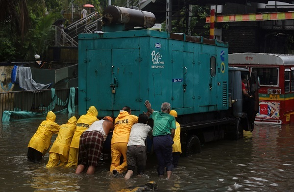 Cops and volunteers push a generator truck through a water-logged street in Mumbai. Photo: Reuters