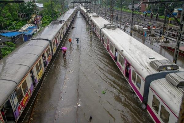 Suburban trains chug on waterlogged tracks. Photo: PTI