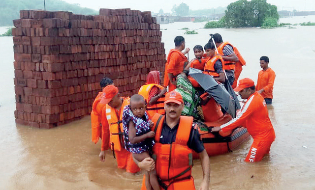 An NDRF team brings villagers to safety. (PIC: NILESH WAIRKAR)