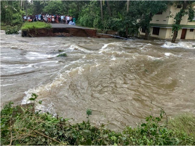 People marooned at a damaged road in a flood-hit area in Thrissur district on Monday, Aug. 20, 2018. (PTI photo)