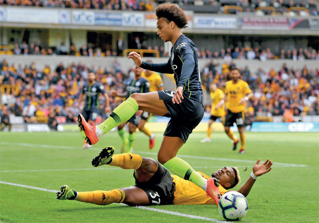 Man City's Leroy Sane and Wolverhampton's Adama Traore battle for the ball during a Premier League match