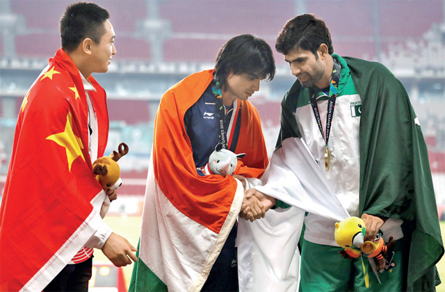 India's javelin champion Neeraj Chopra with China's silver medallist Qizhen Liu (L) and Pakistan's bronze winner Arshad Nadeem during a presentation ceremony at the Asiad