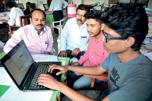 TISS students Surya Karthik and Jayantilal Bagda with senior tribal inspector Vitthal Chavan uploading Mahalabharthi data online.