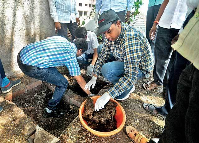 Deputy Collector Ayush Prasad clearing a toilet pit to convince locals that it is safe