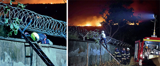 Fire brigade personnel climb a wall and squeeze through the barbed wire to reach the danger zone.