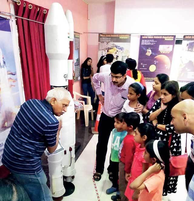 volunteer interacting with visitors at the show in Aditya Garden City