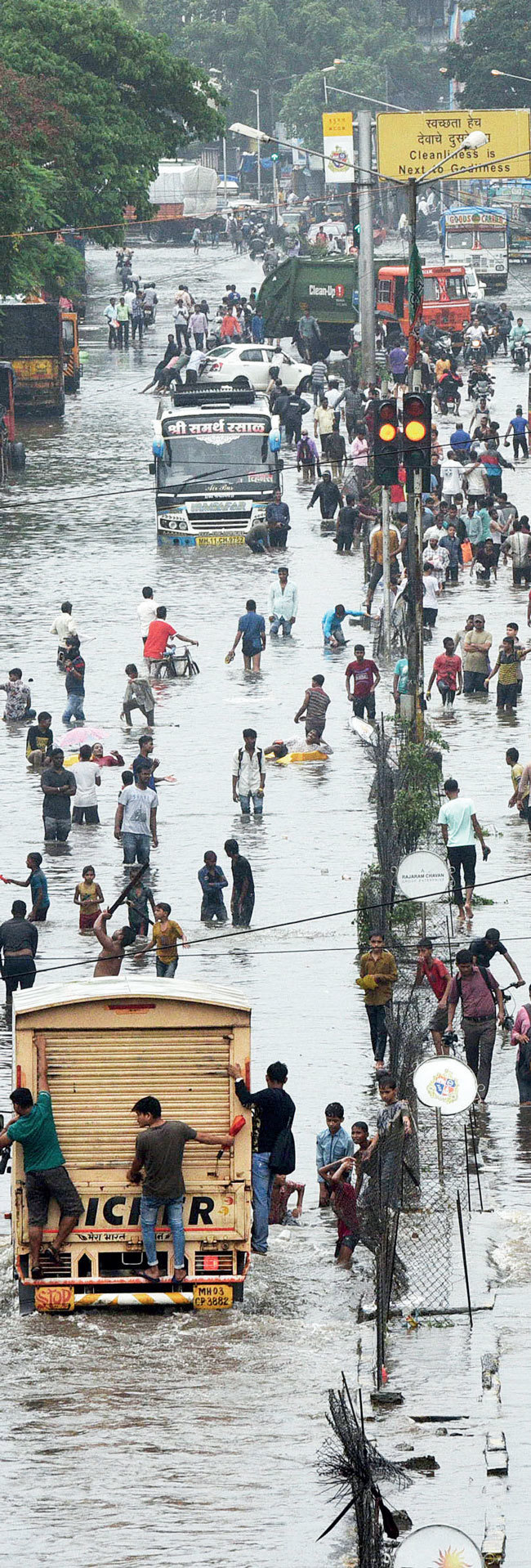 IN DEEP WATER People wade through a flooded LBS Marg road in Kurla's Kamani area on Sunday afternoon —PIC: RAJU SHINDE