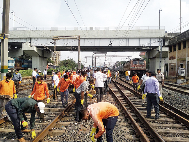 All in a day's work: Volunteers remove filth from the tracks yesterday.