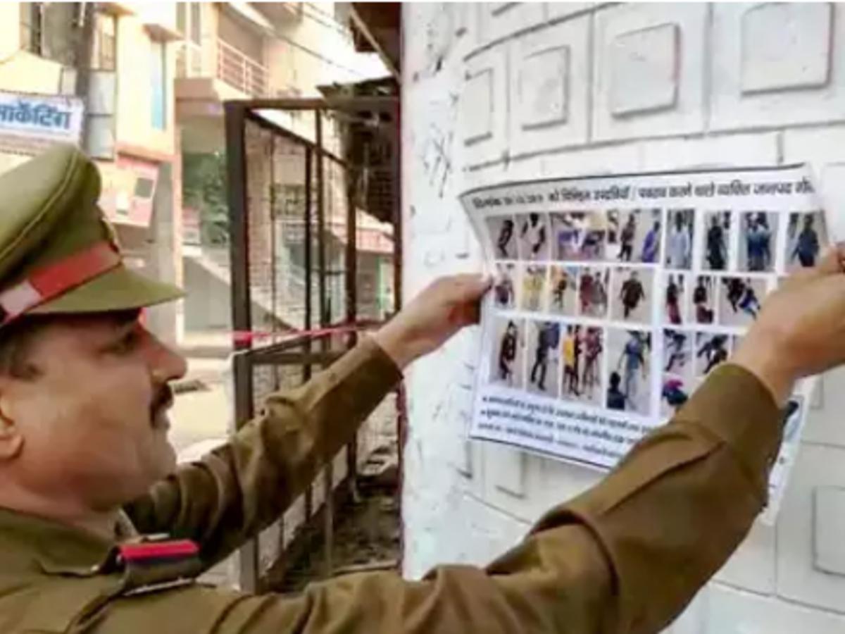 Police man sticks posters PTI