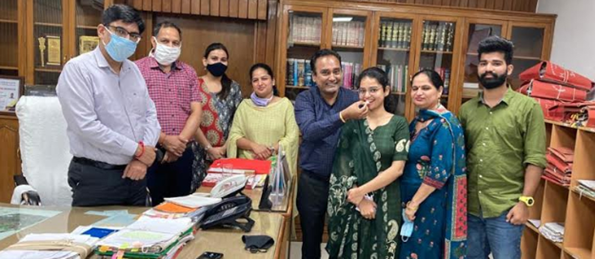 Mahak Swami (in green suit) celebrating achievement with her family at Yamunanagar deputy commissioner (DC) office on Tuesday.
