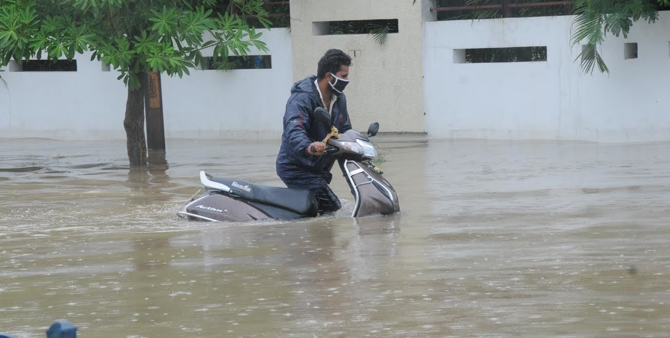 A man pulling his scooter in the floodwater