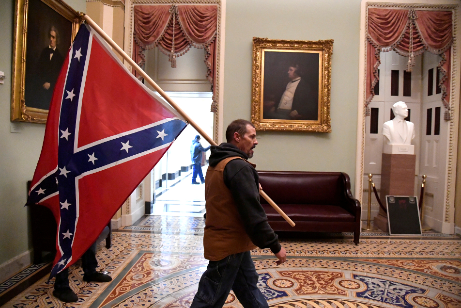 A supporter of President Donald Trump carries a Confederate battle flag Reu 635