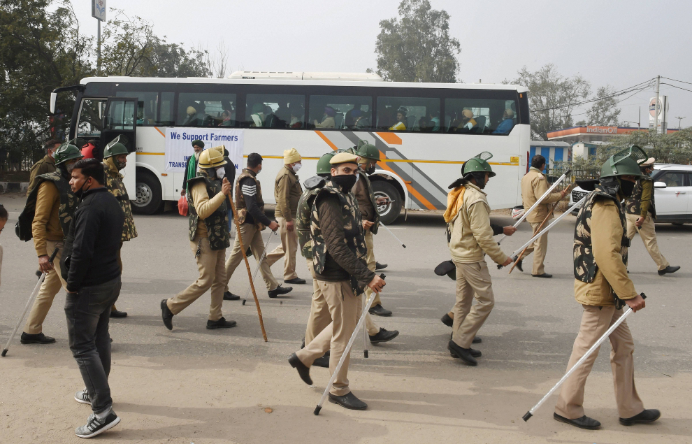 Police personnel walk past a bus with farmer leaders PTI 635