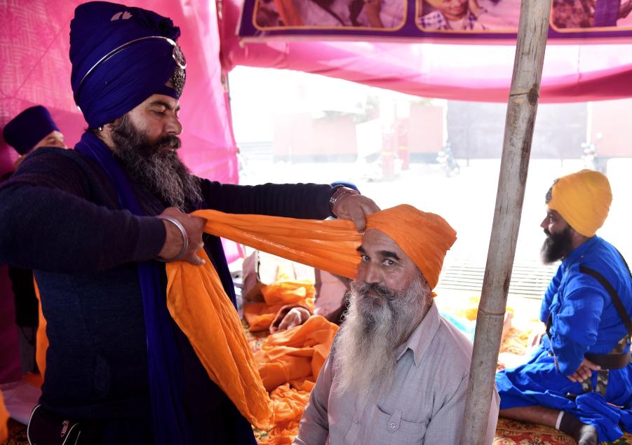 A Nihang Sikh ties turban on the head of a farmer Singhu Border ANI 635