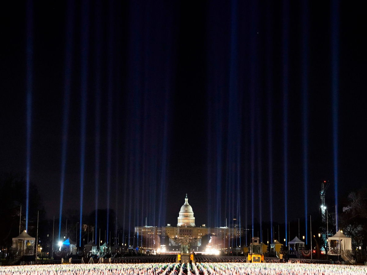 Blue lights are beamed into the sky over the 'Field of Flags' on the National Mall AFP 1200