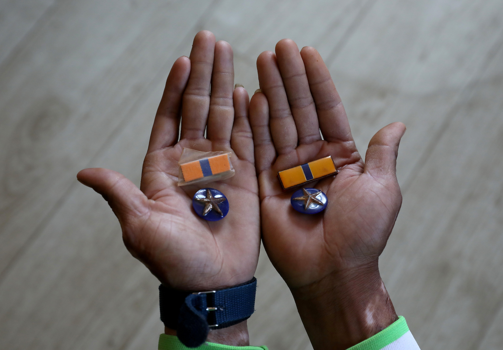 A Myanmar national who said he was a policeman and recently fled to India shows his badges as he poses at an undisclosed location