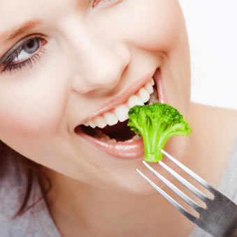 Woman eating broccoli
