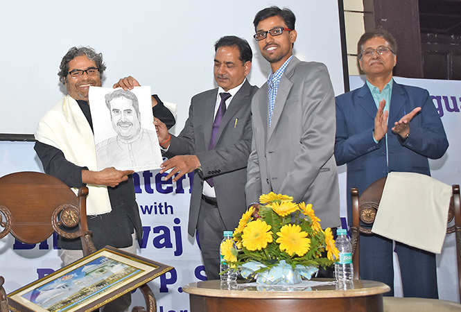 Vishal Bhardwaj (L) posed with a sketch of his made by (R) Abhinav Dwivedi  as SP Singh, LU VC (centre) watches (BCCL/ Farhan Ahmad Siddiqui)