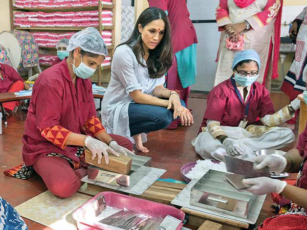 Meghan watches volunteers making sanitary pads at the NGO