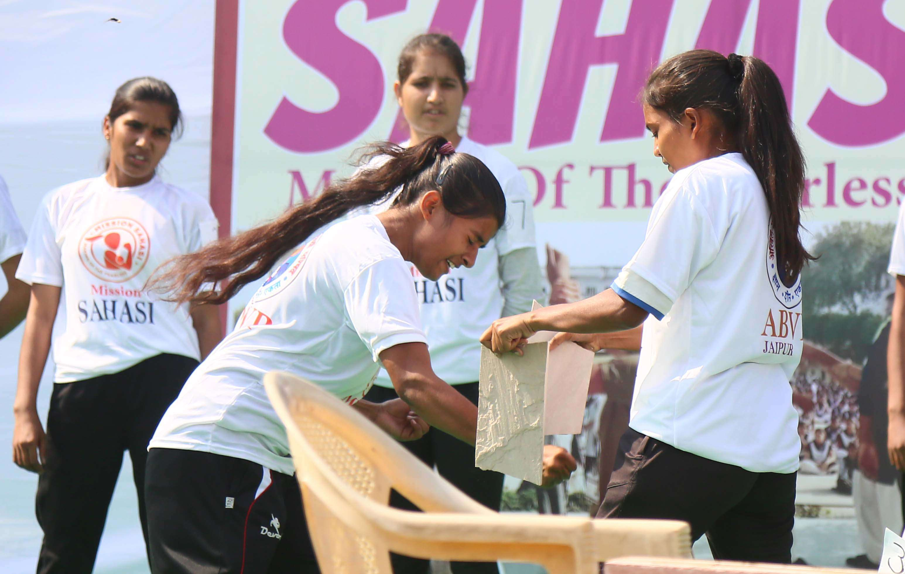 A participant breaks a wooden slab as part of her training