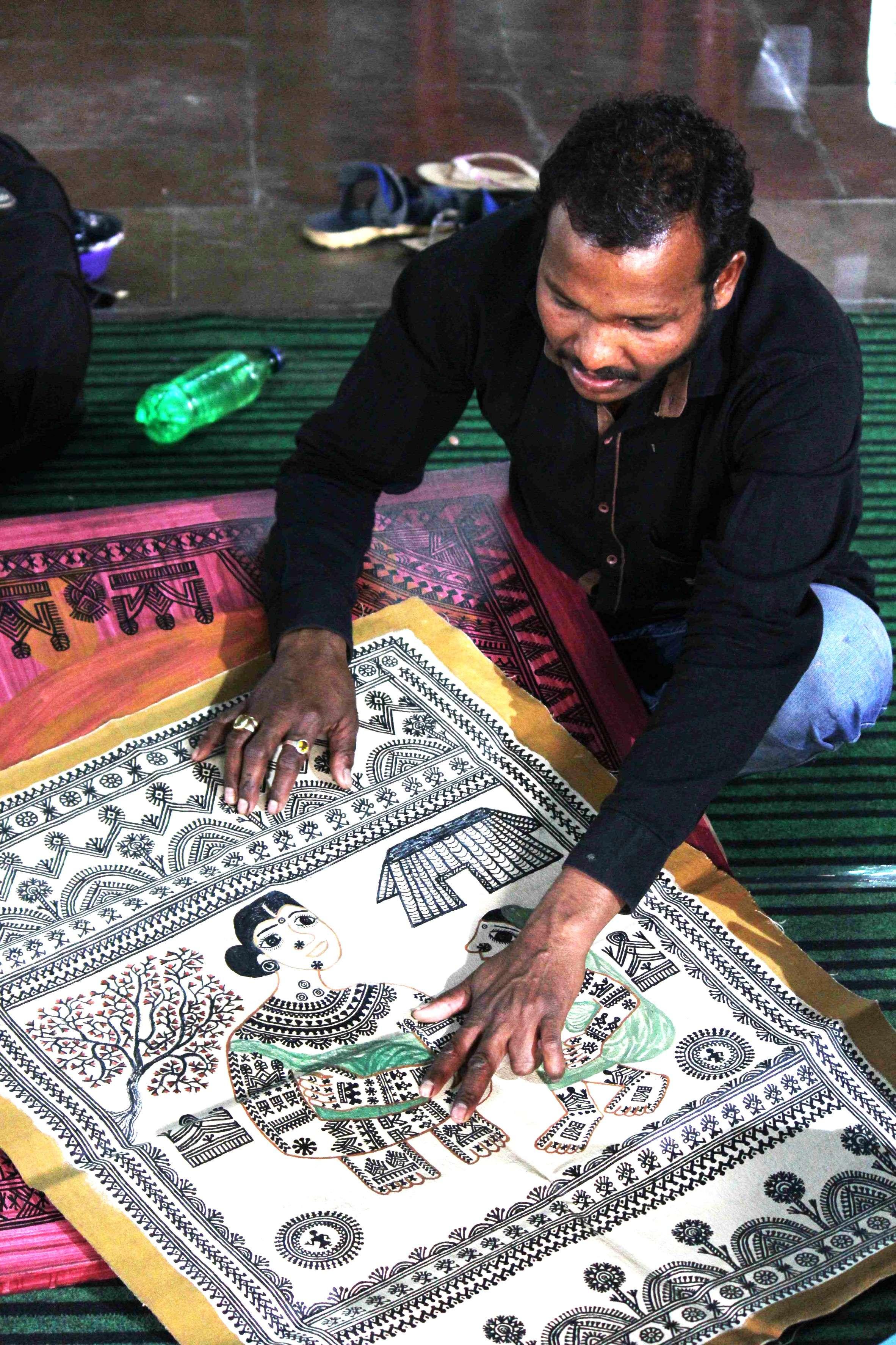 Bhaju paole shows the fabrics he has painted for sale