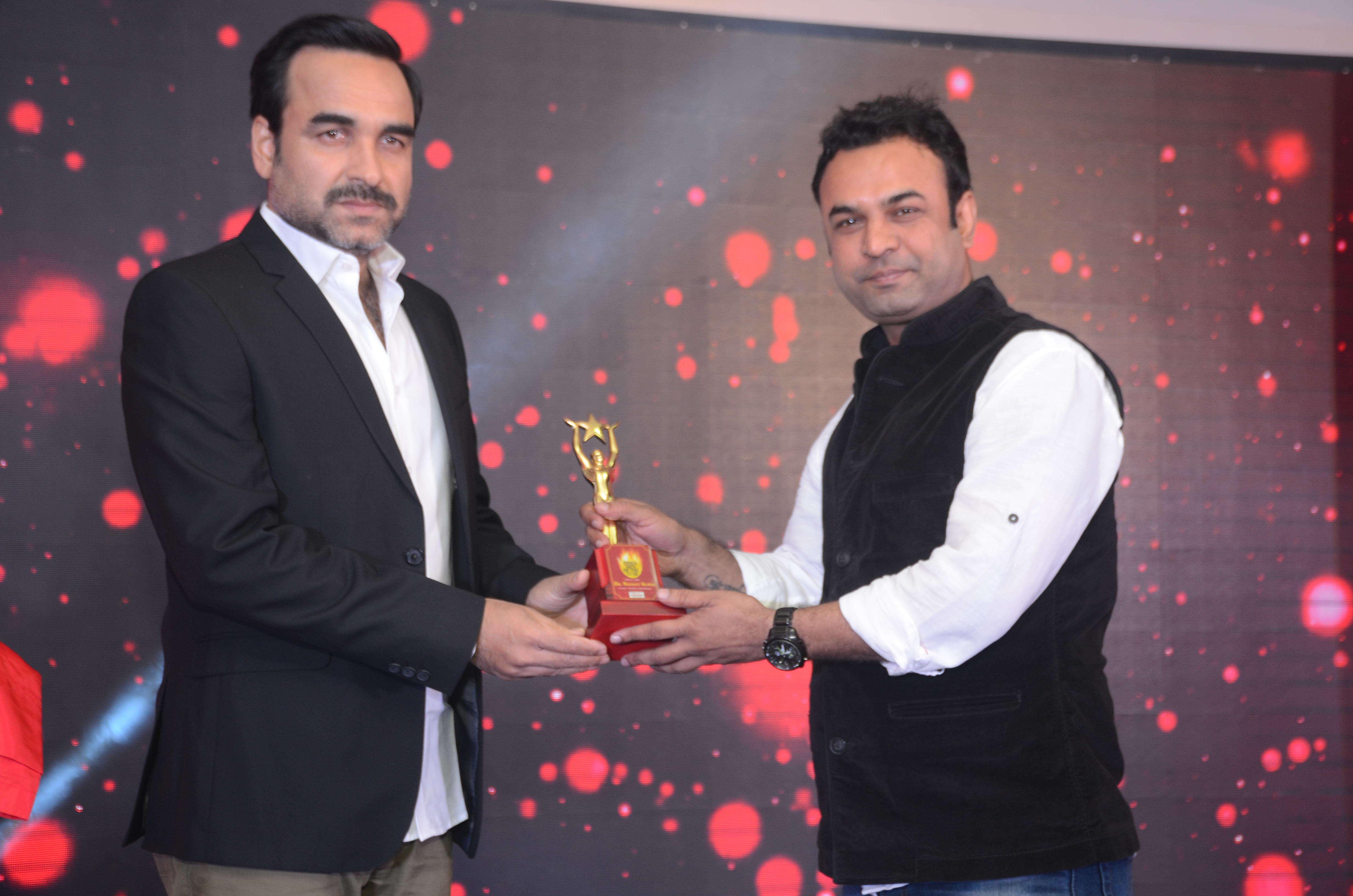 Dr. Navneet Kumar of Vedanta Eye care receives an award from Pankaj Tripathi