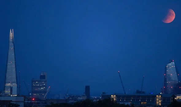 A partial lunar eclipse appears over the London skyline.