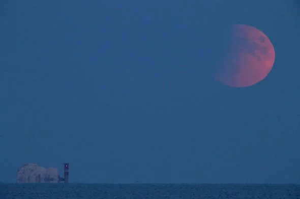 A partial lunar eclipse is visible over the Needles as seen from Dorset.